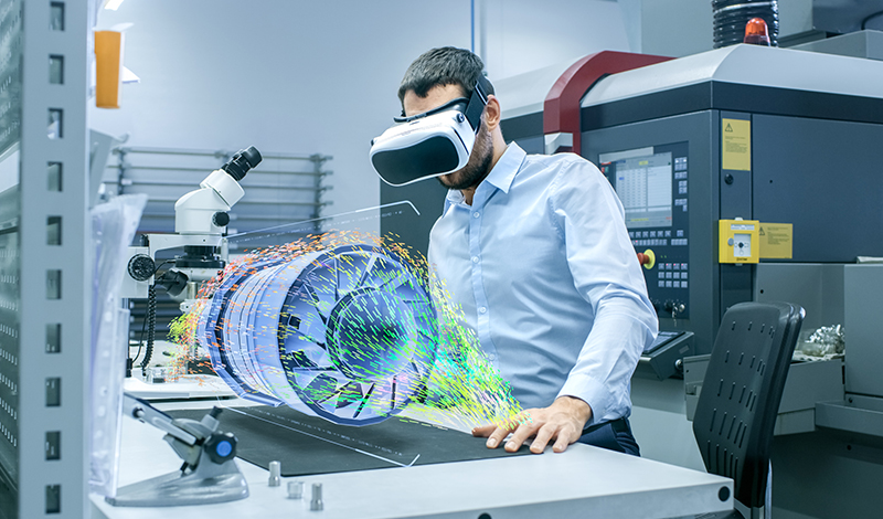 Engineer wearing a virtual reality headset designing a turbine with a holographic projection.