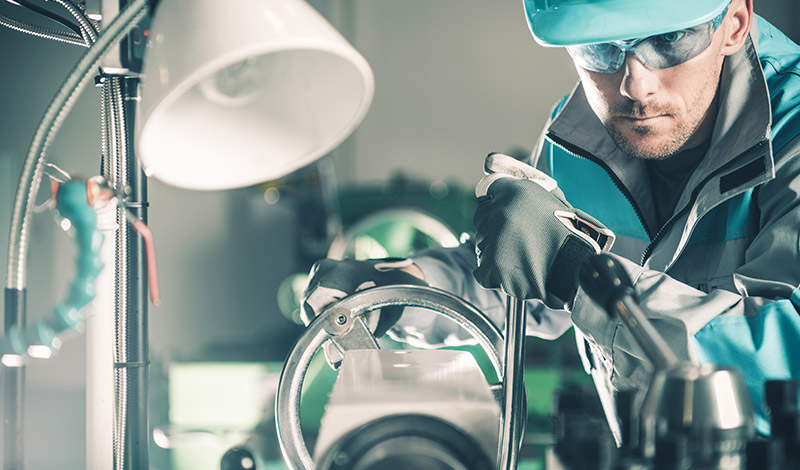 An engineer with a hard hat working with manufacturing equipment.