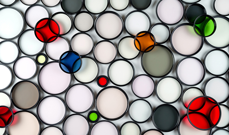Multicolored round glass photographic filters of various sizes on a light background
