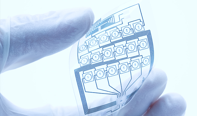 A gloved hand holding a flexible printed electric circuit