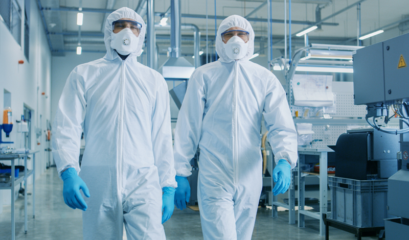 Two employees in hazmat suits in a high-tech manufacturing environment