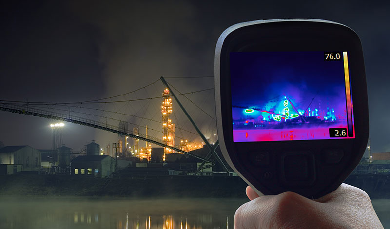 person using heat sensor device on buildings
