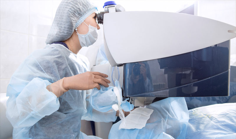 doctor looking through a medical device during surgery