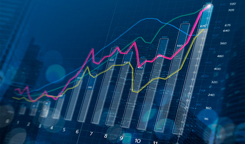 Financial bar chart and growing graphs with depth of field on dark blue background