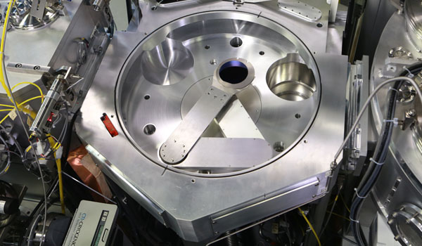 A central wafer handler, with a wafer carrier, holds a semiconductor wafer and moves it between deposition chambers.